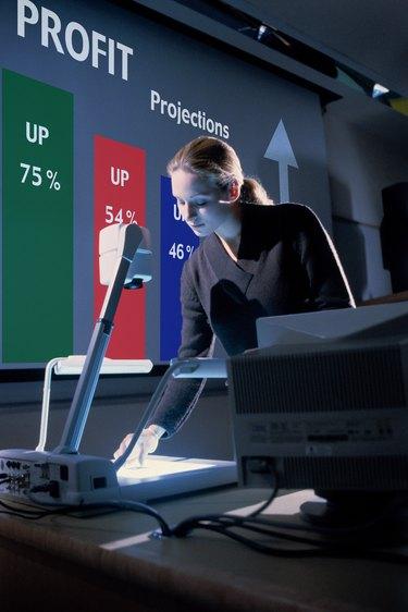 Businesswoman using overhead projector