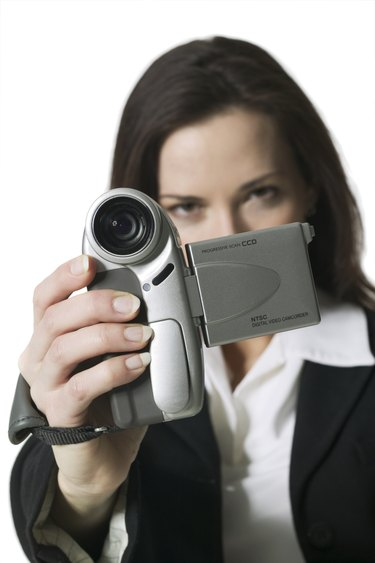 medium shot of a young adult woman as she take home movies with a video camera
