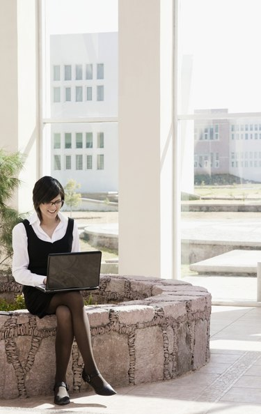 Hispanic businesswoman using laptop outdoors