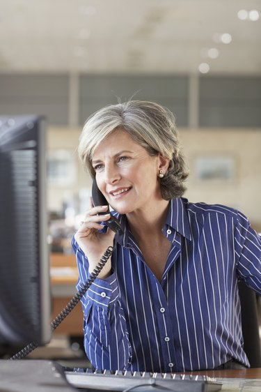 Mature businesswoman using telephone in office