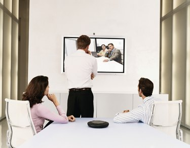 Businessmen and a Businesswoman Watching a Plasma Screen During a Video Conference Meeting