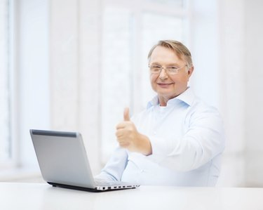 old man with laptop computer showing thumbs up