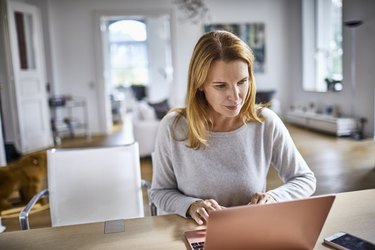 Woman using laptop on table at home