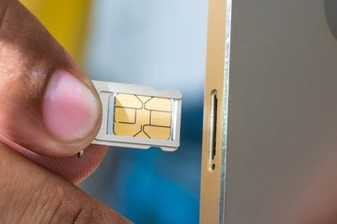 Cropped Image Of Hand Inserting Sim Card In Mobile Phone