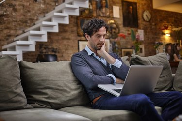 Man using laptop on couch at home
