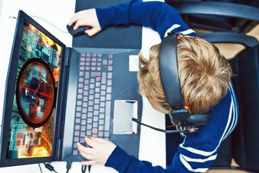 Boy plays video games on gaming computer while wearing headphones