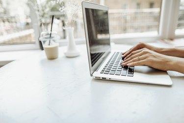 European hands typing on laptop keyabord on white table