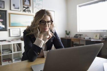 Senior businesswoman entrepreneur working at laptop in studio office