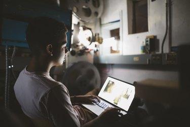 Mixed race tween boy projectionist using laptop in dark movie theater
