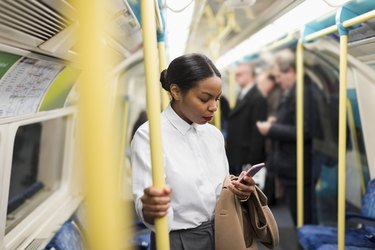 UK, London, businesswoman in underground train looking at cell phone