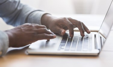 Unrecognizable african american man typing on laptop keyboard in office