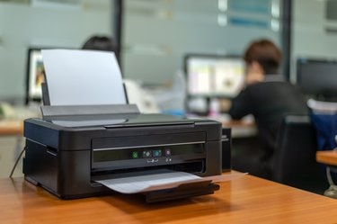 black printer in office with soft-focus and over light in the background