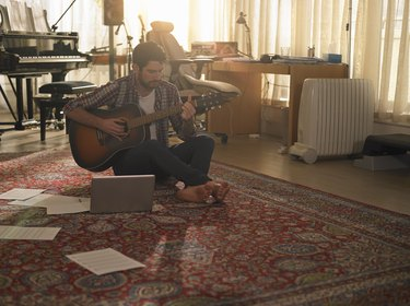 A man playing guitar next to a laptop