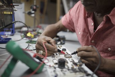 Close up male engineer using soldering iron on electronics
