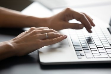 Close up female hands typing on laptop keyboard