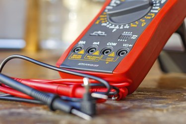 Digital multimeter with probes on a wooden table in the workshop