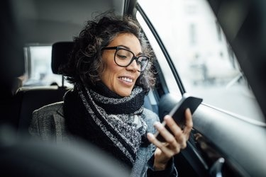 Mature businesswoman using phone while traveling by a taxi