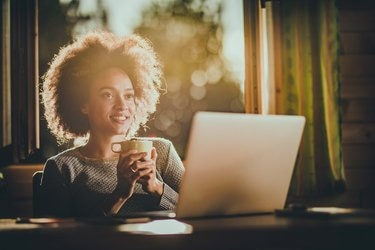 Happy black woman day dreaming while using laptop during her coffee time at home.