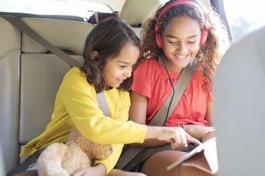 Sisters using digital tablet in back seat of car
