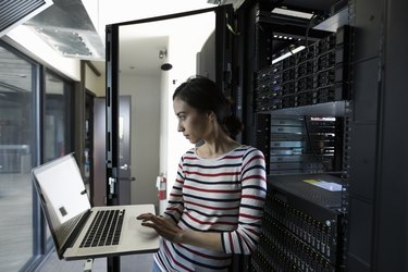 Female Filipino IT technician working at laptop in server room