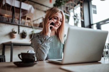 Elegant young woman talking on the phone and using laptop. Low angle view.