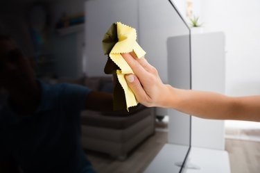 Woman Using Cloth To Clean The Television