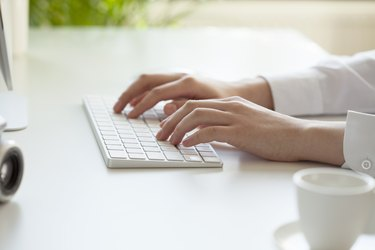 woman hands typing on computer keyboard