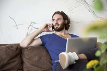 Portrait of young man on the phone sitting on couch in a coffee shop
