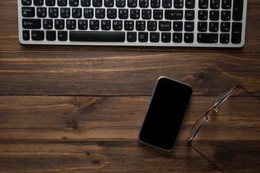 Directly Above Shot Of Keyboard And Mobile Phone With Eyeglasses On Table