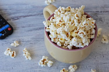 A bowl of delicious caramel popcorn on a white wooden background