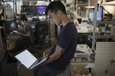 Male engineer working at laptop in workshop