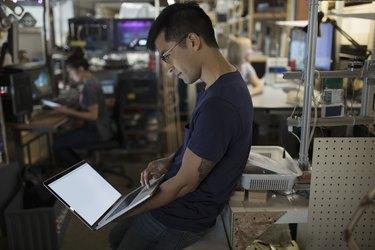 Male engineer working at laptop in workshop