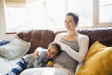 Affectionate mother and toddler son cuddling on living room sofa