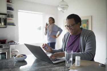 Smiling senior man with credit card paying bills online at laptop at kitchen counter