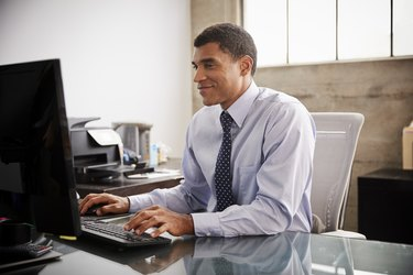 Mixed race businessman using computer in an office