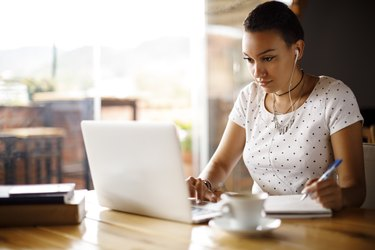 Attractive young woman working on laptop and taking notes at a cafe