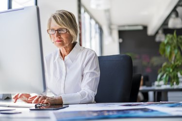 Businesswoman using computer at desk in office