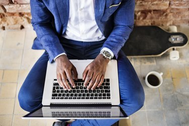 Top view of businessman sitting on longboard using laptop