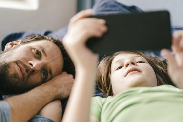 Father and son looking at smartphone together at home