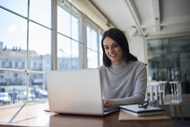 Smiling attractive female freelancer doing remote job using laptop computer