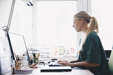 Side view of female nurse working at computer desk against window in office