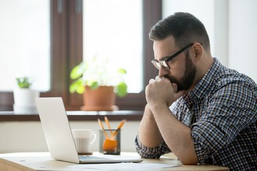 Millennial casual businessman thinking and looking at laptop in office