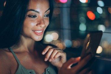 Cute girl using smart phone at night