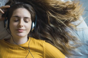 Portrait of smiling young woman lying on bed listening music with headphones