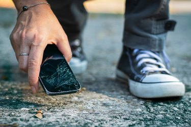 Woman picking up broken smartphone from the ground.