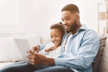 Father and daughter watching movie on tablet