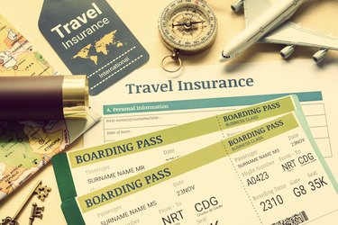 Travel insurance and travel security service concept : Top view of travel insurance application form, business class boarding passes, map, monocular, tag, compass, white model air plane on wood floor.