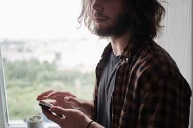 Young bearded man using phone at home