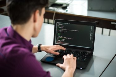 Young man using his laptop to try to solve problem with code