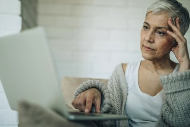 Worried senior woman reading an e-mail on laptop.